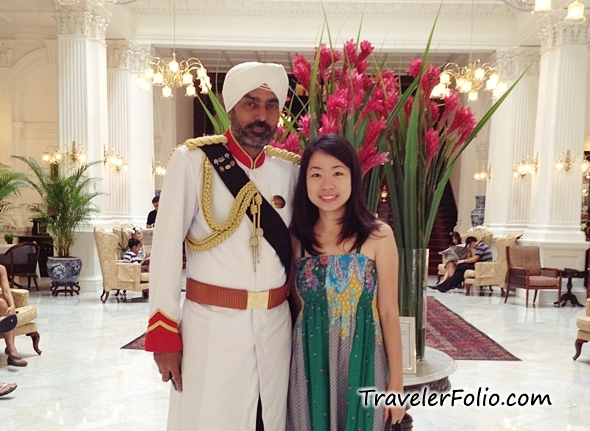 Eunice posing with the doorman at the acclaimed Raffles Hotel in her native Singapore.